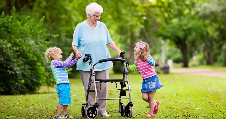 Image of grandmother using a rollator playing with grandchildren